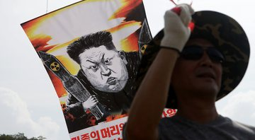 Manifestante carregando um cartaz representando Kim Jong-un, Líder Supremo da Coreia do Norte - Getty Images