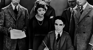 Chaplin sentado e assinando o documento da fundação da United Artists - Wikimedia Commons