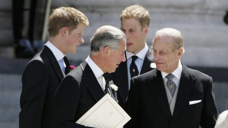 Charles e Philip conversam, com Harry e William ao fundo