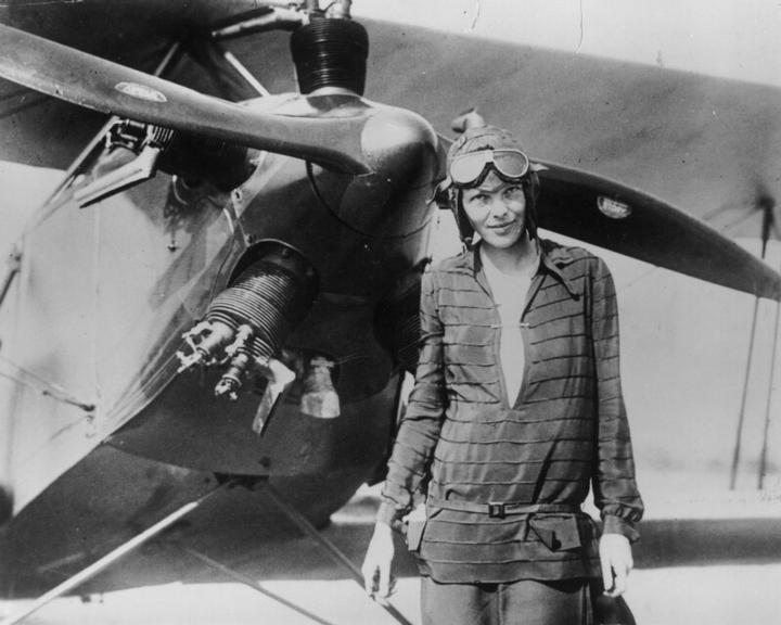 Amelia Earhart posando diante de uma de suas máquinas