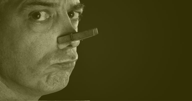 Homem com o nariz tampado