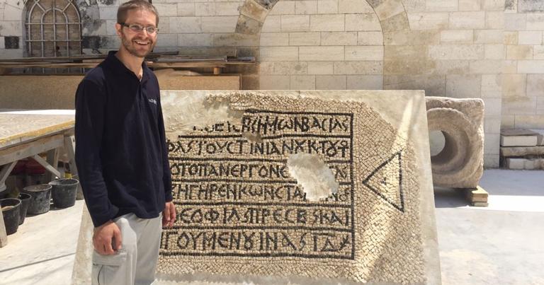 David Gellman, líder da descoberta posando ao lado do mosaico