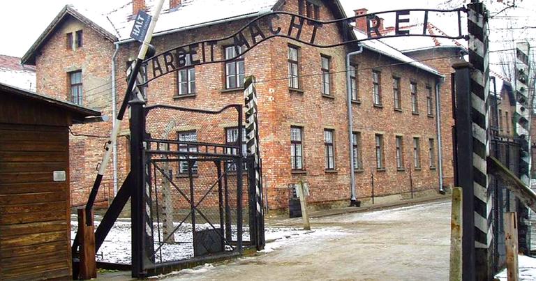 """Portão na entrada do campo de concentração de Auschwitz com a frase Arbeit Macht Frei (""""o trabalho liberta"""")"""