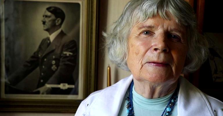 Vera Oredsson posando na frente de um retrato de Adolf Hitler