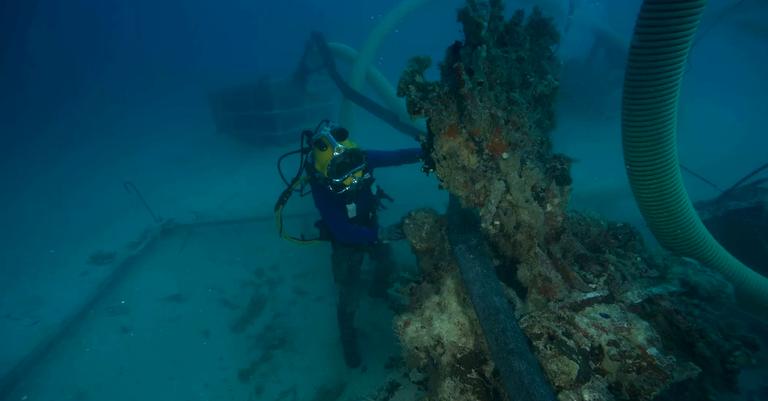 Mergulhador examina o local onde os restos foram encontrados