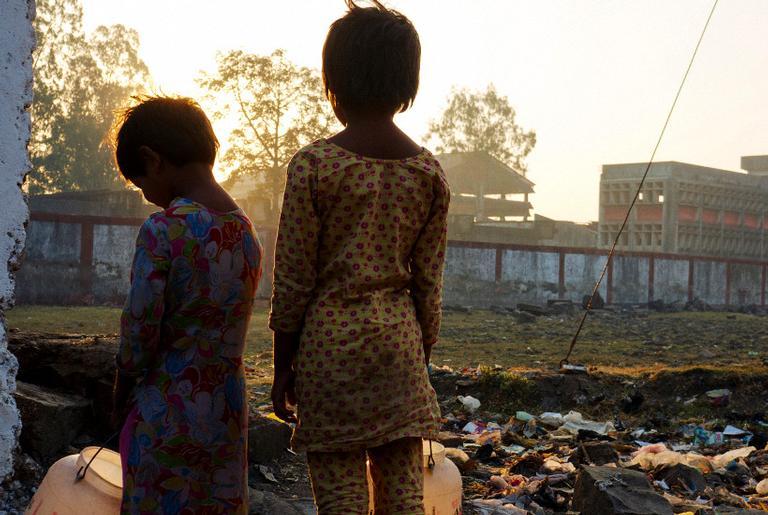 Duas crianças indianas olhando para o desastre