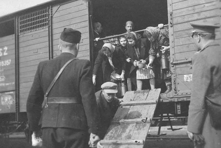 Guarda nazista força judeus a entrarem em um dos trens, em 1942
